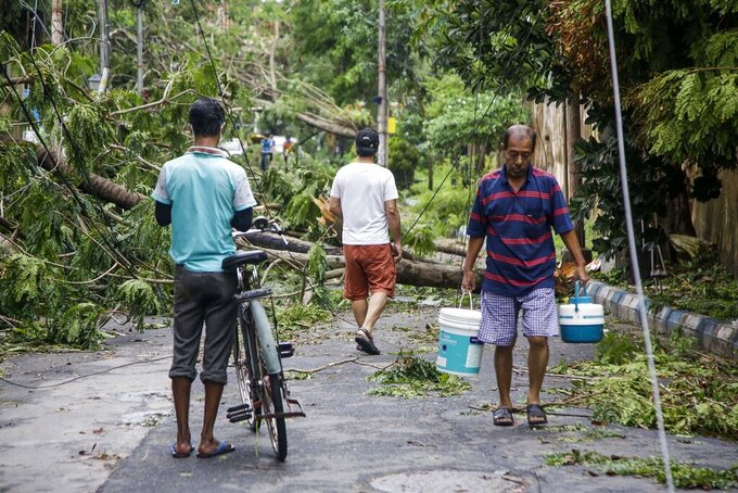An Indian man carries drinking water from a nearby source and walks past trees fallen after Cyclone Amphan hit the region in Kolkata, India, Thursday, May 21, 2020. A powerful cyclone ripped through densely populated coastal India and Bangladesh, blowing off roofs and whipping up waves that swallowed embankments and bridges and left entire villages without access to fresh water, electricity and communications. (AP Photo/Bikas Das)