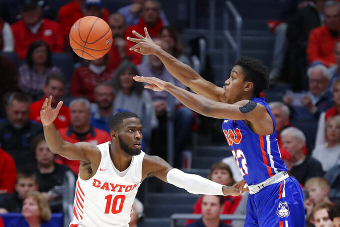 Houston Baptist's Jalon Gates (22) passes over Dayton's Jalen Crutcher (10) during the first half of an NCAA college basketball game, Tuesday, Dec. 3, 2019, in Dayton, Ohio. (AP Photo/John Minchillo)