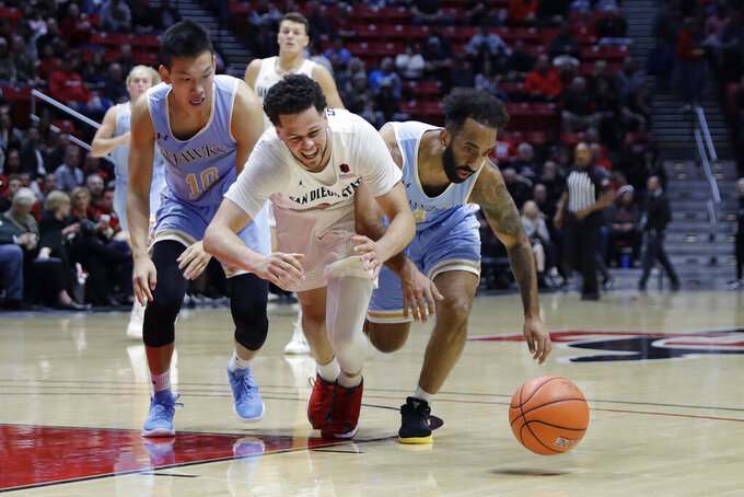San Diego State's Jordan Schakel, center, battles for a loose ball against San Diego Christian's Jonathan Chapotin, right, and Zhang Weijie, left, during the first half of an NCAA college basketball game Wednesday, Dec. 18, 2019, in San Diego. (AP Photo/Gregory Bull)