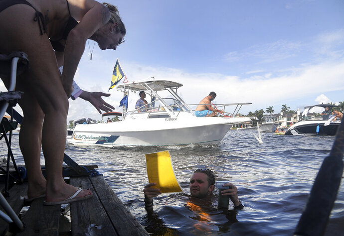 Colette Murray takes a swim up order Jay's Sand Bar Floating BBQ, serving pork nachos and alligator bites to hungry boaters and bikini-wearing partiers on the sandbar in Ft. Lauderdale, Fla., on Saturday, Oct. 10, 2020. (Mike Stocker/South Florida Sun-Sentinel via AP)