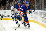 Tampa Bay Lightning center Brayden Point (21) and New York Islanders defenseman Scott Mayfield (24) chase down the puck during the first period of Game 3 of the NHL hockey Stanley Cup semifinals, Thursday, June 17, 2021, in Uniondale, N.Y. (AP Photo/Frank Franklin II)