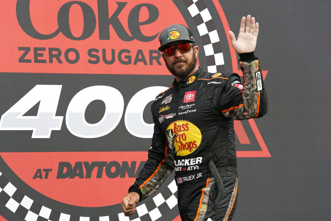 Martin Truex Jr. waves to fans during driver introductions before the NASCAR Cup Series auto race at Daytona International Speedway, Saturday, Aug. 28, 2021, in Daytona Beach, Fla. (AP Photo/John Raoux)