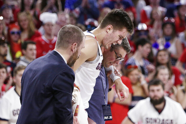 Gonzaga forward Filip Petrusev, center, is helped off the court by team staff after suffering an injury during the second half of an NCAA college basketball game against BYU in Spokane, Wash., Saturday, Jan. 18, 2020. Gonzaga won 92-69. (AP Photo/Young Kwak)