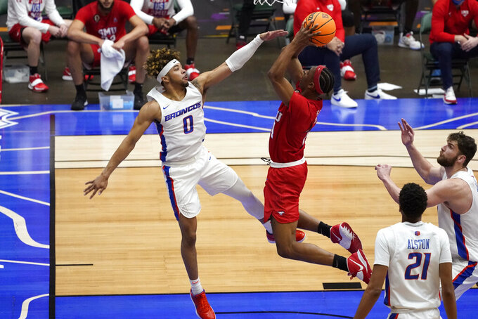 SMU guard William Douglas shoots over Boise State guard Marcus Shaver Jr. (0) during the second half of an NCAA college basketball game in the first round of the NIT, Thursday, March 18, 2021, in Frisco, Texas. (AP Photo/Tony Gutierrez)