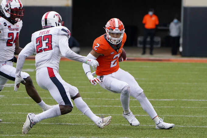 Oklahoma State wide receiver Tylan Wallace (2) carries past Texas Tech defensive back DaMarcus Fields (23) in the second half of an NCAA college football game in Stillwater, Okla., Saturday, Nov. 28, 2020. (AP Photo/Sue Ogrocki)