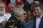 Brazil's former President Luiz Inacio Lula da Silva kisses his girlfriend Rosangela da Silva after exiting the the Federal Police headquarters where he was imprisoned on corruption charges in Curitiba, Brazil, Friday, Nov. 8, 2019. Da Silva walked out of a Curitiba prison Friday, less than a day after the Supreme Court ruled that a person can be imprisoned only after all the appeals have been exhausted. (AP Photo/Leo Correa)