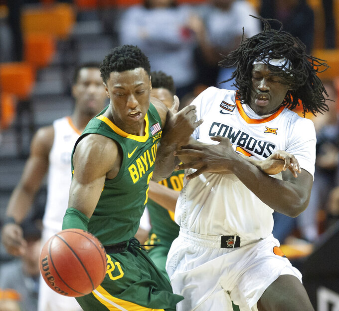 Oklahoma State guard Isaac Likekele, right, grabs the arm of Baylor guard Devonte Bandoo during the first half of an NCAA college basketball game in Stillwater, Okla., Saturday, Jan. 18, 2020. (AP Photo/Brody Schmidt)