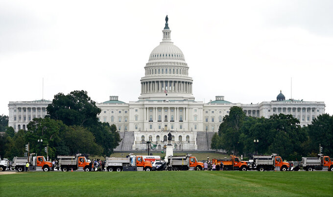 """Dozens of dump trucks form a barrier as security measures are put into place before a rally near the U.S. Capitol in Washington, Saturday, Sept. 18, 2021. The rally was planned by allies of former President Donald Trump and aimed at supporting the so-called """"political prisoners"""" of the Jan. 6 insurrection at the U.S. Capitol. (AP Photo/Gemunu Amarasinghe)"""