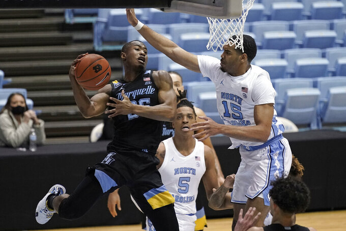 Marquette guard Koby McEwen (25) tries to shoot while North Carolina forward Garrison Brooks (15) defends during the second half of an NCAA college basketball game in Chapel Hill, N.C., Wednesday, Feb. 24, 2021. (AP Photo/Gerry Broome)