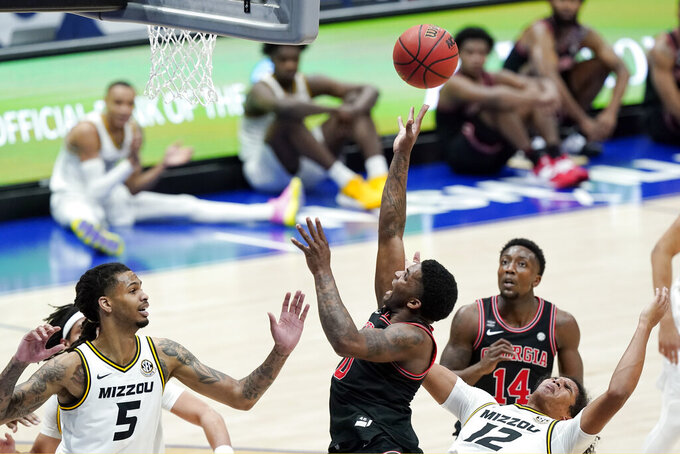 Georgia's K.D. Johnson (0) reaches for the ball between Missouri's Mitchell Smith (5) and Dru Smith (12) in the first half of an NCAA college basketball game in the Southeastern Conference Tournament Thursday, March 11, 2021, in Nashville, Tenn. (AP Photo/Mark Humphrey)