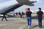 In this handout photo provided by the Philippines Bureau of Immigration Public Information Office, (PIO), U.S. Marine Lance Cpl. Joseph Scott Pemberton, in grey shirt, is escorted as he boards a U.S. military plane in Manila, Philippines on Sunday Sept. 13, 2020. A U.S. Marine convicted of killing a Filipino transgender woman was deported Sunday after a presidential pardon cut short his detention in a case that renewed outrage over a pact governing American military presence in the Philippines. (Bureau of Immigration PIO via AP)