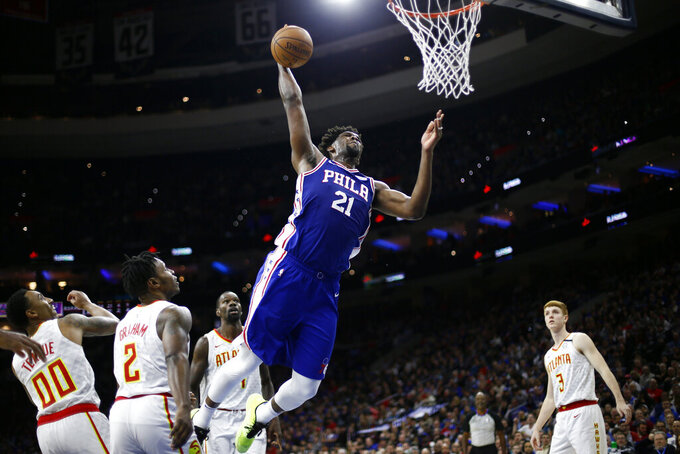 FILE - Philadelphia 76ers' Joel Embiid (21) goes up for a dunk during the second half of an NBA basketball game against the Atlanta Hawks in Philadelphia, in this Monday, Feb. 24, 2020, file photo. The 76ers have kept their trust in Joel Embiid .A person familiar with the situation told The Associated Press Embiid and the Sixers agreed on a four-year, $196 million contract extension that will take the All-Star center through the 2026-2027 season. The person spoke  on condition of anonymity because the deal was not expected to be formally announced later Tuesday, Aug. 17, 2021. (AP Photo/Matt Slocum, File)