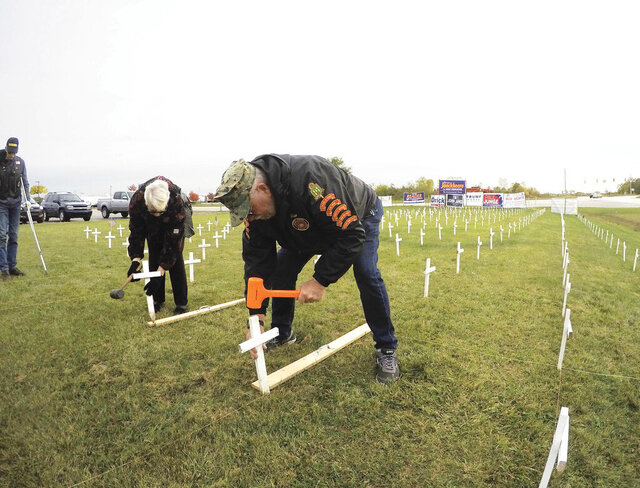 American Legion Auxiliary member Pat Washburn, at left, and Marine Corps League and American Legion member Ron Brooks are among a group of volunteers planting 22 crosses in front of the American Legion Devereaux Post 141 in Howell Township, Mich., Wednesday, Oct. 14, 2020. The effort was part of a 30 day project to represent the approximately 22 deaths by suicide of American veterans nationally each day, as estimated by the Veterans Administration, according to Veterans Service officer Jon Luker. (Gillis Benedict/Livingston County Daily Press & Argus via AP)