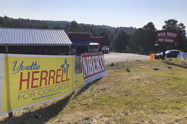 A campaign sign for Republican U.S. House hopeful Yvette Herrell sits in front of the Wild West Ski Shop in Ruidoso, N.M., on Oct. 6, 2020. New Mexico is on the verge of electing the nation's largest all-female of color U.S. House delegation but the close race in the state's southern district, where Ruidoso sits, is grabbing the most attention. (AP Photo/ Russell Contreras)
