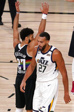 Denver Nuggets' Jamal Murray (27) keeps his arms in position as Utah Jazz's Rudy Gobert (27) walks past after Gobert scored a basket and drew a foul on the play during the second half an NBA first round playoff basketball game, Tuesday, Sept. 1,2020, in Lake Buena Vista, Fla. (AP Photo/Mark J. Terrill)