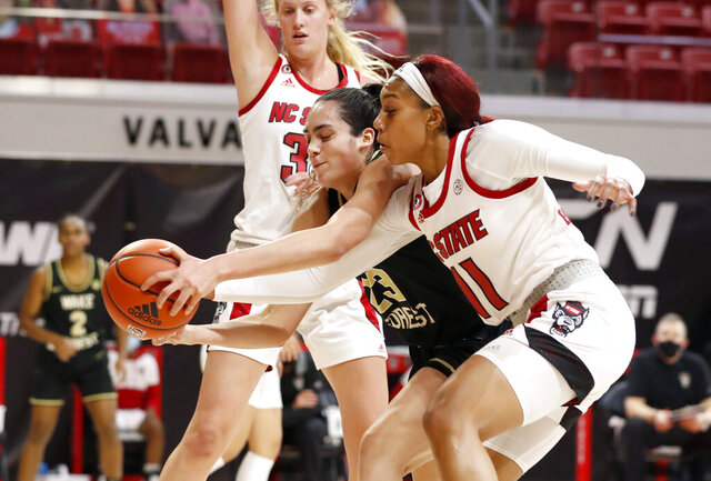 Wake Forest's Christina Morra (23) and North Carolina State's Jakia Brown-Turner (11) go after the ball during the first half of an NCAA college basketball game, Thursday, Dec. 17, 2020, in Raleigh, N.C. (Ethan Hyman/The News & Observer via AP)