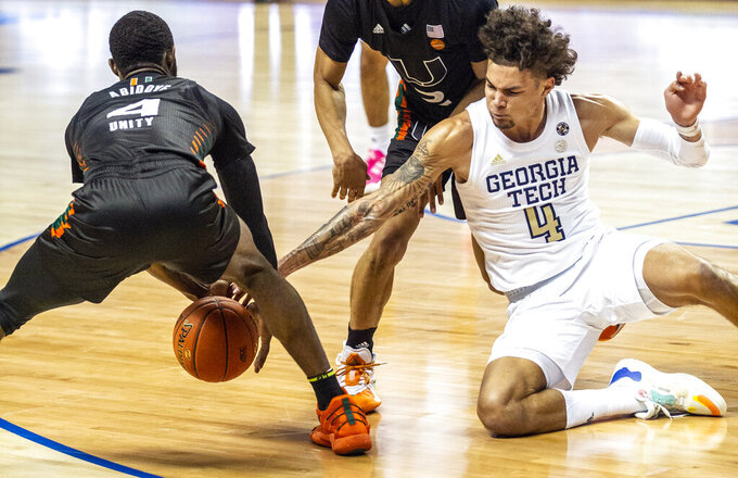 Miami's Elijah Olaniyi, left, and Georgia Tech's Jordan Usher(4) scramble for a loose ball during an NCAA college basketball game in the quarterfinal round of the Atlantic Coast Conference tournament in Greensboro, N.C., Thursday, March 11, 2021. (Woody Marshall/News & Record via AP)