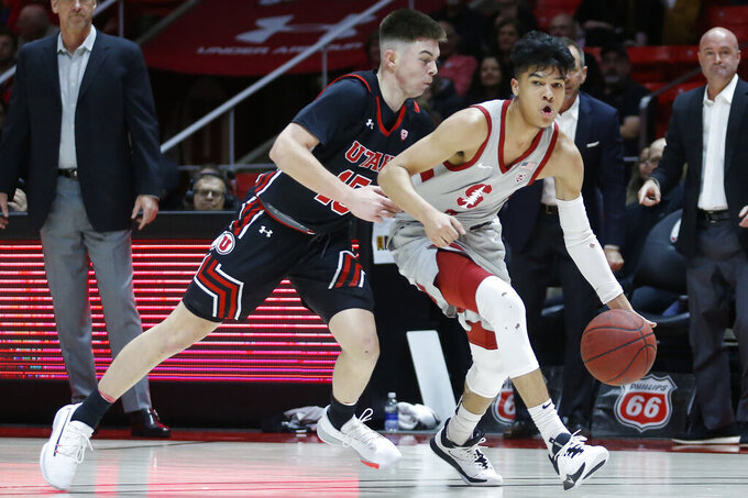 Stanford guard Tyrell Terry, right, drives as Utah guard Rylan Jones, left, defends in the first half during an NCAA college basketball game Thursday, Feb. 6, 2020, in Salt Lake City. (AP Photo/Rick Bowmer)