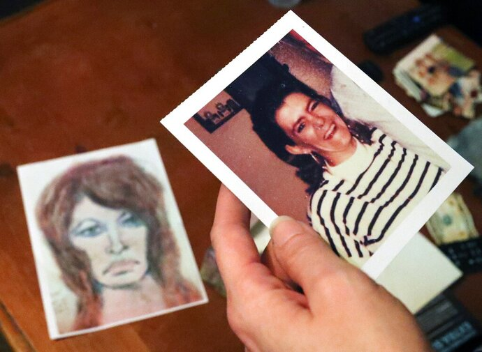 In this Thursday, Oct. 10, 2019 photo, Tonya Maslar holds an old photograph of her mother Roberta Tandarich taken before her death in 1991 in Ravenna, Ohio. Tandarich's body was found dumped at Firestone Metro Park in 1991. A sketch of Tandarich drawn by serial killer Samuel Little, who claims Tandarich was one of his many victims, lies in the background. (Jeff Lange/Akron Beacon Journal via AP)