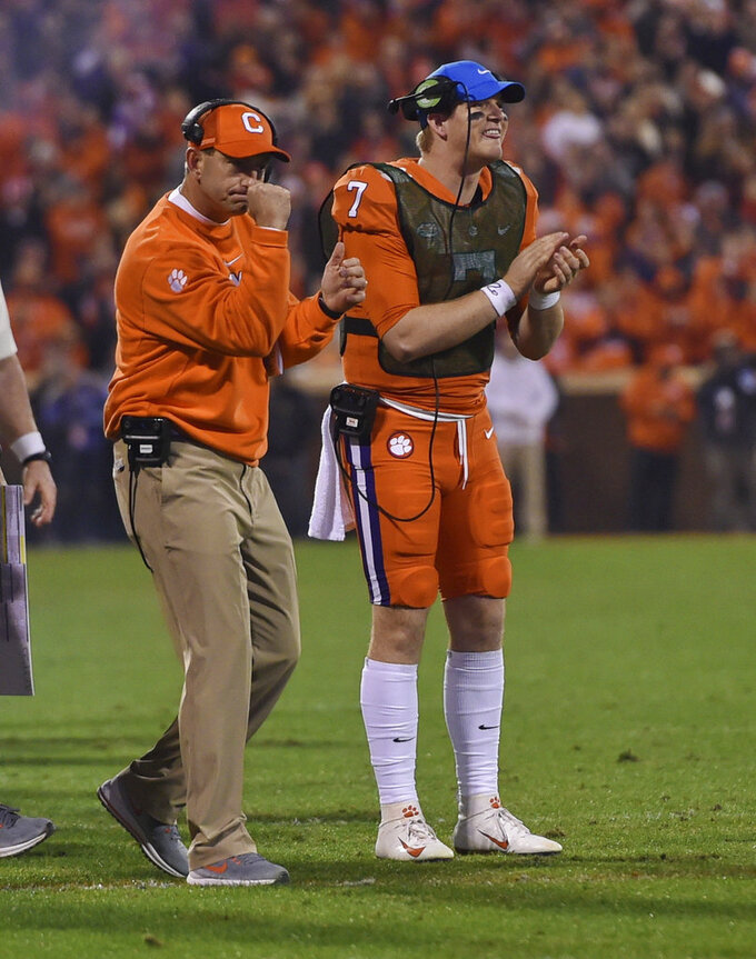 Clemson head coach Dabo Swinney, left, and quarterback Chase Brice celebrate a touchdown during the first half of an NCAA college football game against South Carolina Saturday, Nov. 24, 2018, in Clemson, S.C. (AP Photo/Richard Shiro)