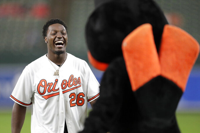 Green Bay Packers NFL rookie safety Darnell Savage Jr., left, laughs with Oriole Bird after throwing out a ceremonial first pitch prior to a baseball game between the Baltimore Orioles and the Washington Nationals, Wednesday, July 17, 2019, in Baltimore. (AP Photo/Julio Cortez)
