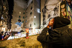 People gather and light candles under a mural of soccer legend Diego Maradona, in Naples, Italy, Wednesday, Nov. 25, 2020. Diego Maradona has died. The Argentine soccer great was among the best players ever and who led his country to the 1986 World Cup title before later struggling with cocaine use and obesity. He was 60. (Alessandro Garofalo/LaPresse via AP)