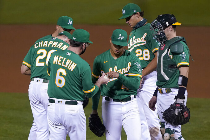 Oakland Athletics starting pitcher Jesus Luzardo, center, is taken out by manager Bob Melvin (6) during the fifth inning of a baseball game against the San Diego Padres in Oakland, Calif., Friday, Sept. 4, 2020. (AP Photo/Tony Avelar)
