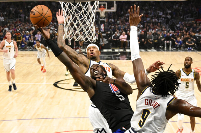Los Angeles Clippers forward Montrezl Harrell, left, shoots as Denver Nuggets forward Torrey Craig, center, and forward Jerami Grant defend during the first half of an NBA basketball game Friday, Feb. 28, 2020, in Los Angeles. (AP Photo/Mark J. Terrill)