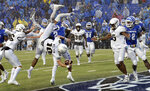 Central Florida quarterback McKenzie Milton (10) dives over Memphis defensive back's Josh Perry (4) and T.J. Carter (2) as he scores the go-ahead touchdown on a 7-yard run in the second half of an NCAA college football game Saturday, Oct. 13, 2018, in Memphis, Tenn. Central Florida won 31-30. (AP Photo/Mark Zaleski)