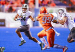Colorado State running back Izzy Matthews (24) runs with the ball against the defensive pressure of Boise State linebacker Curtis Weaver (99) in the first half of an NCAA college football game, Friday, Oct. 19, 2018, in Boise, Idaho. (AP Photo/Steve Conner)