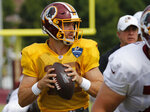 FILE - In this Monday, Aug. 5, 2019 file photo, Washington Redskins quarterback Colt McCoy (12) looks for a receiver during the Washington Redskins NFL football training camp in Richmond, Va. Case Keenum's foot injury could put him in danger of starting at quarterback for the Washington Redskins on Sunday, Sept. 29, 2019 at the New York Giants. If Keenum can't play, the 0-3 Redskins will either turn to Colt McCoy or ask first-round pick Dwayne Haskins to make his NFL debut. (AP Photo/Steve Helber, File)