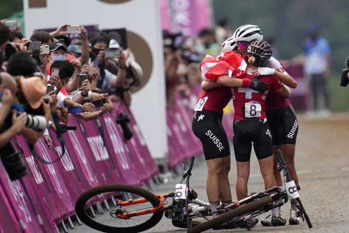 Jolanda Neff of Switzerland hugs teammates Sina Frei (8) who won silver, and Linda Indergand (19) who won bronze, for a sweep of the podium for Switzerland, at the finish line the women's cross-country mountain bike competition at the 2020 Summer Olympics, Tuesday, July 27, 2021, in Izu, Japan. (AP Photo/Christophe Ena)