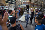 Anti-government protesters celebrate after they removed part of a concrete wall that was installed by security forces to prevent them from reaching the government palace in Beirut, Lebanon, Thursday, July 2, 2020. Major retailers in Lebanon announced Thursday they will temporarily close in the face of an increasingly volatile currency market and their inability to set prices while the local currency tumbles before the dollar. (AP Photo/Hassan Ammar)