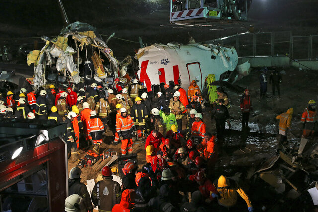 Rescue members evacuate an injured person from the wreckage of a plane after it skidded off the runway at Istanbul's Sabiha Gokcen Airport, in Istanbul, Wednesday, Feb. 5, 2020. The plane skidded off as it tried to land in bad weather, crashing into a field and breaking into pieces. Passengers had to evacuate through cracks in the smashed plane and authorities said 120 people were sent to the hospital with injuries. (AP Photo/Emrah Gurel)