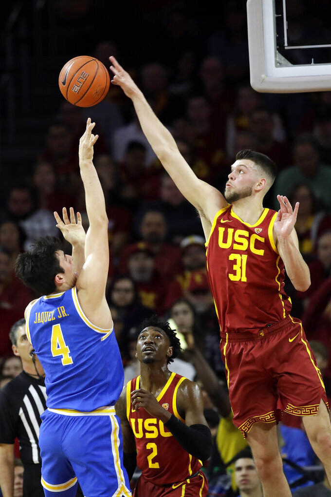 Southern California forward Nick Rakocevic (31) blocks a shot from UCLA guard Jaime Jaquez Jr. (4) during the first half of an NCAA college basketball game Saturday, March 7, 2020, in Los Angeles. (AP Photo/Marcio Jose Sanchez)