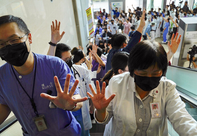 Medical workers display their palm with five fingers, signifying the five demands of protesters and chanted slogans as they stood in the foyer of the hospital before moving to different floors of the building at the Prince of Wales Hospital in Hong Kong, Monday, Sept. 16, 2019. The anti-government protests have taken place since June and increasingly have been marked by violence and clashes with police. (AP Photo/Vincent Yu)