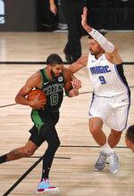 Boston Celtics forward Jayson Tatum (0) drives to the basket against Orlando Magic center Nikola Vucevic (9) during the first half of an NBA basketball game Sunday, Aug. 9, 2020, in Lake Buena Vista, Fla. (Kim Klement/Pool Photo via AP)