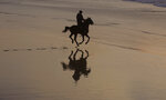 A Palestinian man rides a horse during sunset at the beach, in Gaza City, Saturday, Feb. 22, 2020. The beach is one of the few open public spaces in this densely populated city. (AP Photo/Hatem Moussa)