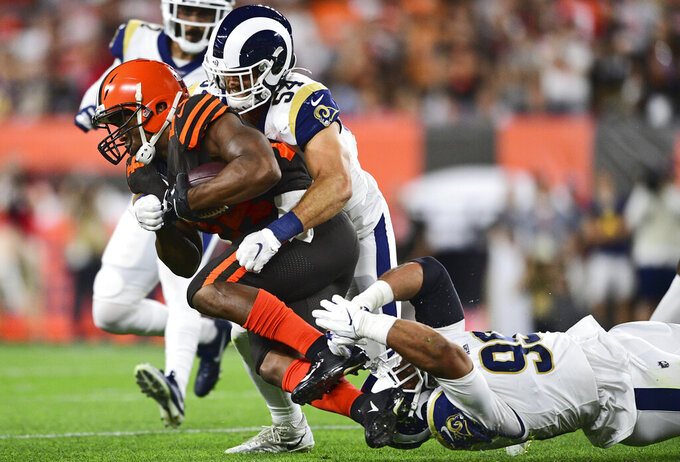 Cleveland Browns running back Nick Chubb (24) runs for 8-yard gain under pressure from Los Angeles Rams linebacker Bryce Hager (54) and defensive tackle Aaron Donald during the first half of an NFL football game Sunday, Sept. 22, 2019, in Cleveland. (AP Photo/David Dermer)