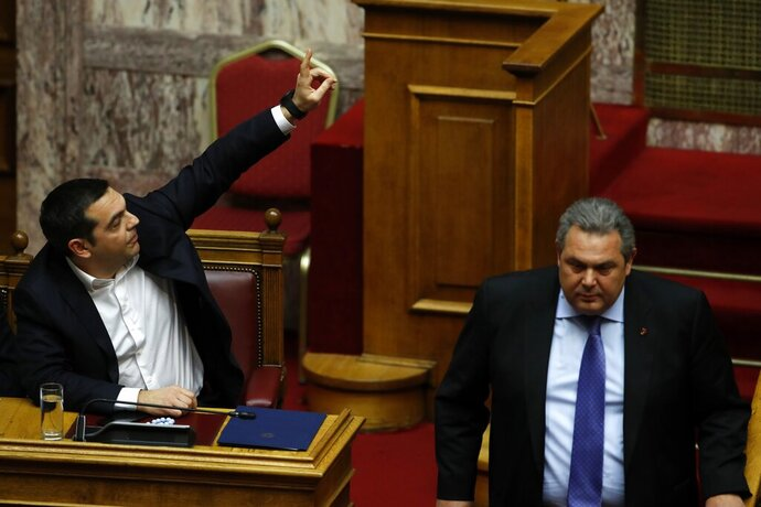 Greece's Prime Minister Alexis Tsipras, left, raises his hand as former defense minister Panos Kammenos leaves the podium during a parliament session in Athens, Friday, Feb. 8, 2019. Greek lawmakers are set Friday to approve Macedonia's NATO accession, ending a process to normalize relations between the two neighbors and anchor the country — renamed North Macedonia — firmly within the western sphere of influence. (AP Photo/Thanassis Stavrakis)