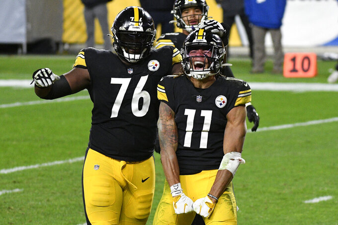 Pittsburgh Steelers wide receiver Chase Claypool (11) celebrates with Chukwuma Okorafor (76) his scoring on a 5-yard touchdown pass from quarterback Ben Roethlisberger during the second half of an NFL football game against the Cincinnati Bengals in Pittsburgh, Sunday, Nov. 15, 2020. (AP Photo/Don Wright)