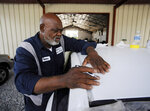 In this Tuesday, July 9, 2019 photo, Walter Porter, Mayor of Epes, Ala., works on a vehicle at his automotive body shop in Epes.  The town is still poor despite having a port along the 234-mile-long Tennessee-Tombigbee Waterway, and Porter said dreams of development from the $2 billion project remain unfulfilled more than three decades after it opened. (AP Photo/Jay Reeves)