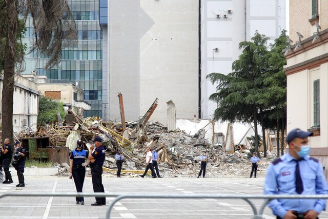 Police guard during the demolition of the national theater building in Tirana, Monday, May 18, 2020. Albanian artists and opposition party supporters gathered for a second day Monday to protest the demolition of the crumbling National Theater building in the capital, which has triggered strong political tension amid a major heritage debate. (AP Photo/Gent Onuzi)