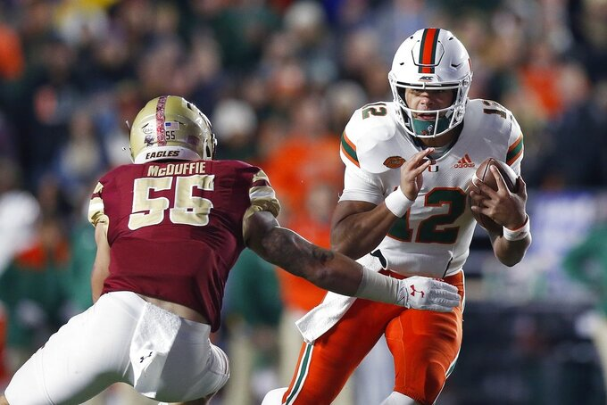 Miami quarterback Malik Rosier (12) carries the ball against Boston College offensive lineman Isaiah McDuffie (55) during the first half of an NCAA college football game in Boston, Friday, Oct. 26, 2018. (AP Photo/Michael Dwyer)