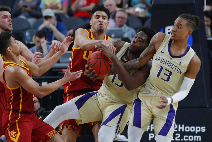 From front left to right, Southern California's Derryck Thornton, Bennie Boatwright, Washington's Noah Dickerson and Hameir Wright scramble for the ball during the second half of an NCAA college basketball game in the quarterfinal round of the Pac-12 men's tournament Thursday, March 14, 2019, in Las Vegas. (AP Photo/John Locher)