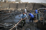 Workers use a water hose to put down a fire at a vehicle oil store hit by Saudi-led airstrikes in Sanaa, Yemen, Thursday, July 2, 2020. (AP Photo/Hani Mohammed)