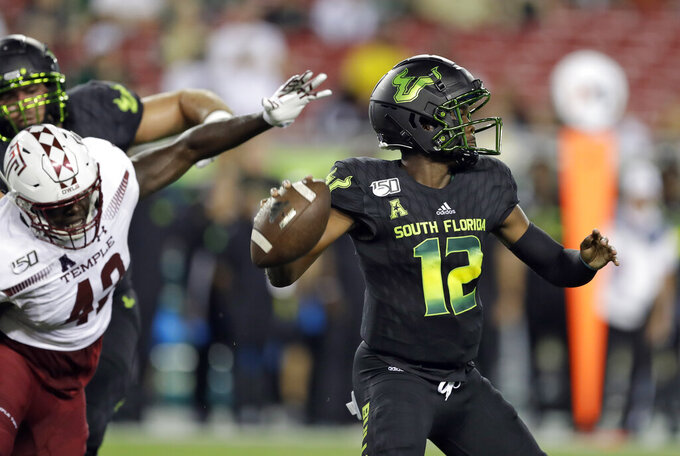 South Florida quarterback Jordan McCloud (12) looks for a receiver as he is pressured by Temple defensive end DeAndre Kelly (42) during the first half of an NCAA college football game Thursday, Nov. 7, 2019, in Tampa, Fla. (AP Photo/Chris O'Meara)