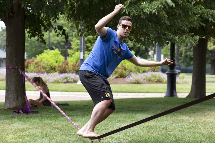 Frankie Colavito works out on a balance line in Piers Park, Saturday, June 27, 2020, in Boston. (AP Photo/Michael Dwyer)