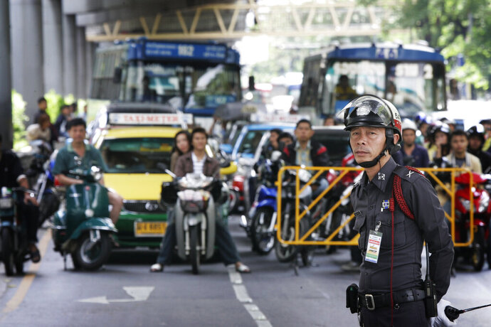 FILE - In this June 12, 2006, file photo, Bangkok traffic police officer holds back traffic as a royal motorcade passes by in Bangkok Monday, June 12, 2006. Thailand's king has directed police to reduce the blockage of traffic during royal motorcades. (AP Photo/David Longstreath, FIle)