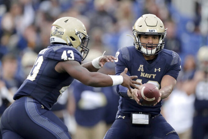 Navy quarterback Malcolm Perry, right, hands off to fullback Nelson Smith during the first half of an NCAA college football game against Tulane, Saturday, Oct. 26, 2019, in Annapolis. (AP Photo/Julio Cortez)